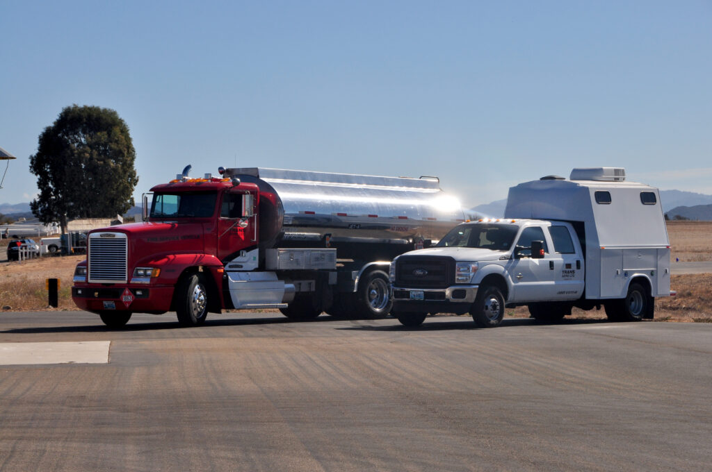 A fuel truck and additional support truck are parked side by side
