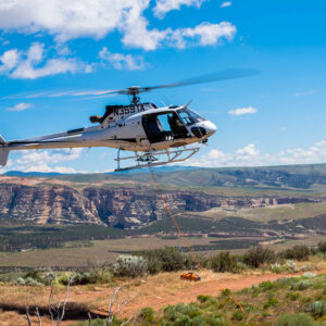 An AS350 B3 helicopter in flight with mountains in the background