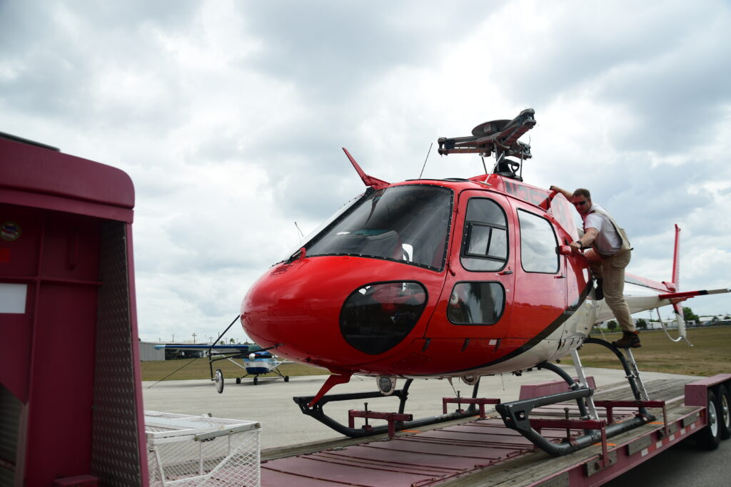 An AS350 B3 helicopter with blades removed sits on a trailer