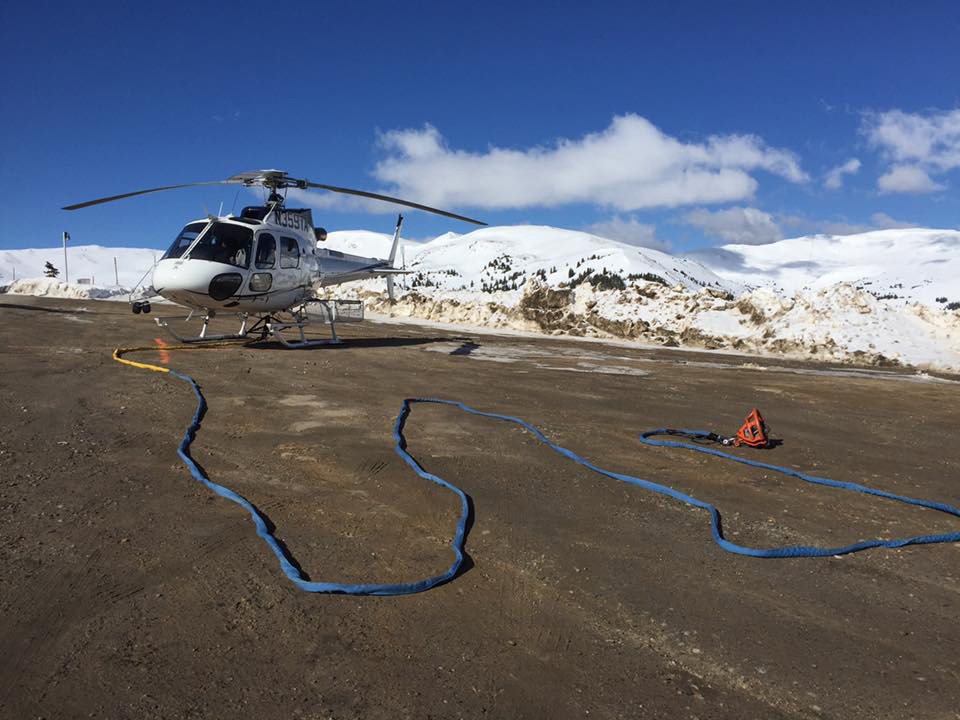 An AS350 B3 helicopter sits on a mountain with a long line