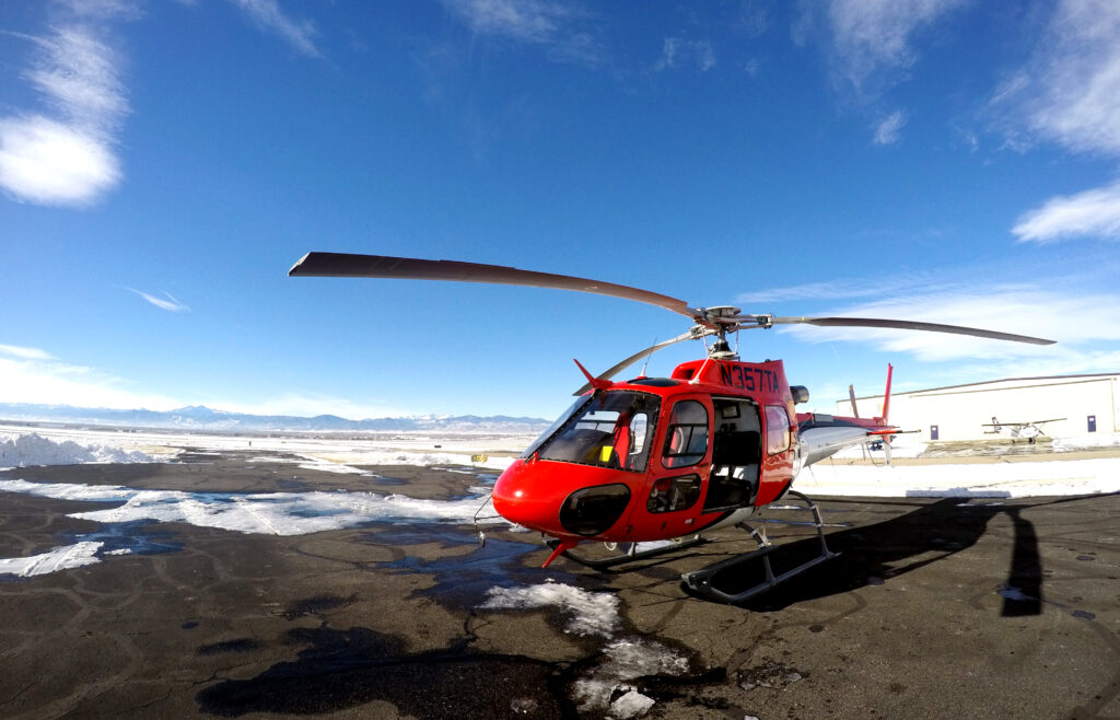 A red AS350 B3 helicopter sits on a snowy helipad