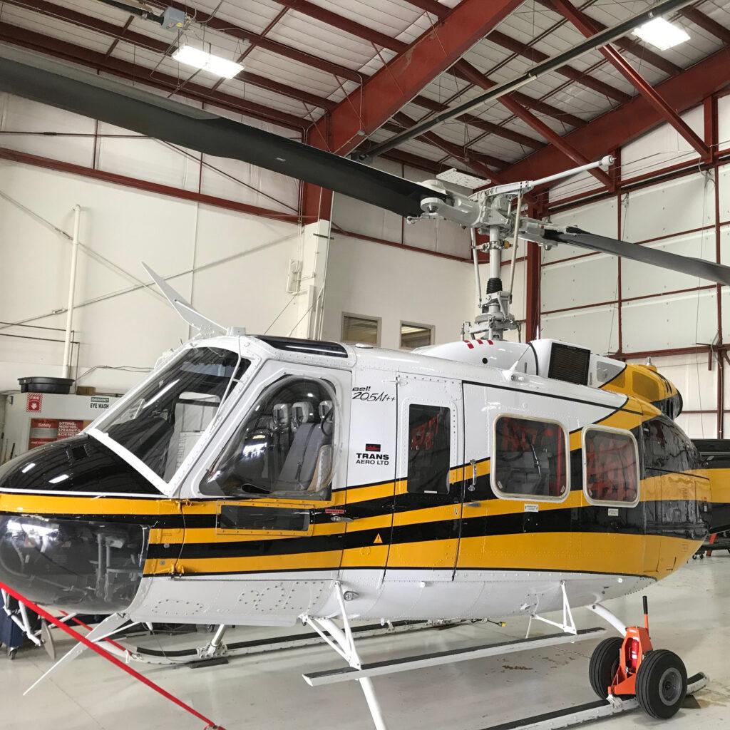 A Bell 205A1 sits in a hangar