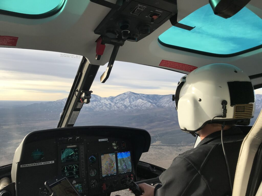 Shows the interior of a helicopter and the pilot mid-flight, with mountains in the distance