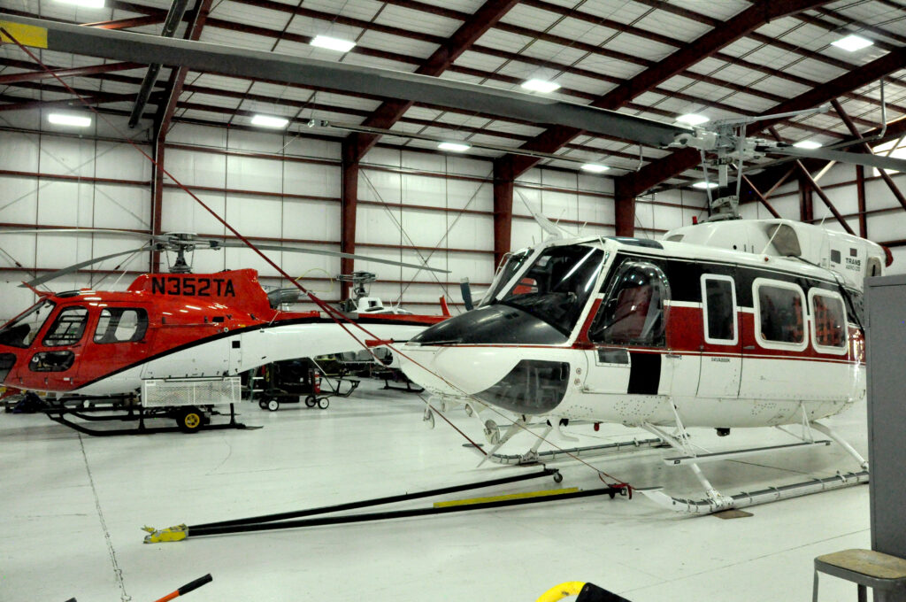 An AS350 B3 and Bell 212 helicopter sit in a hangar